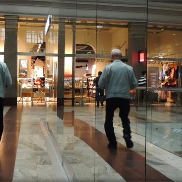Spiegelung im Stockholmer Bahnhof-ein Mann läuft paralell an einer Glaswand..